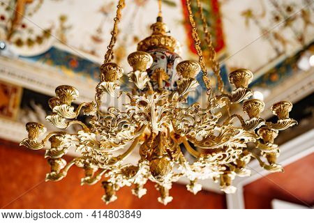 Close-up Of An Antique Gold Italian Chandelier. A Chandelier-chandelier On Gilded Chains Hangs Again