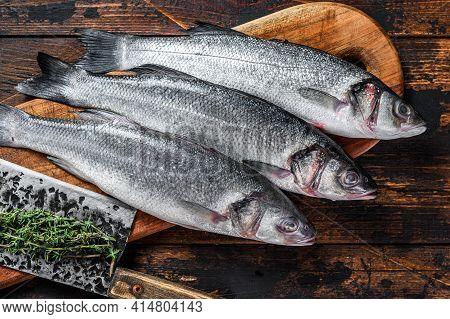 Fresh Raw Fish Seabass On A Cutting Board. Dark Wooden Background. Top View