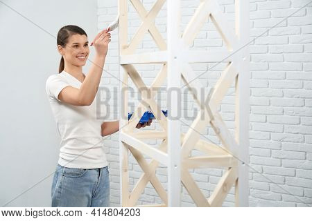 Smiling Young Brunette Woman Painting Wooden Rack At Home. Concept Of Improvement Rack.