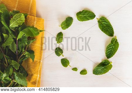 Organic Fresh Mint. Washed Mint Leaves On A Yellow Towel On A White Wooden Background. Ornament From
