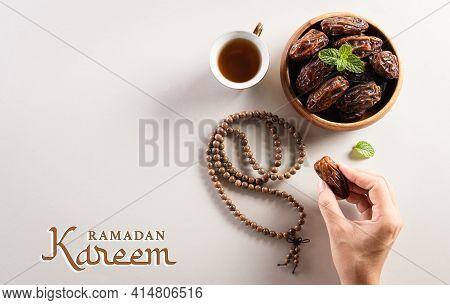 Ramadan Kareem Background Concept,  Hands Picking Up Dates Fruit, Tea And Rosary Beads. Flat Lay Bac