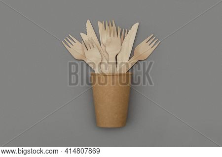 Wooden Fork And Knife In Paper Cup On Gray Background, Top View. Eco Friendly Disposable Tableware F