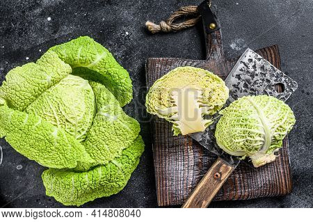 Cut Fresh Healthy Savoy Cabbage On Cutting Board. Black Background. Top View