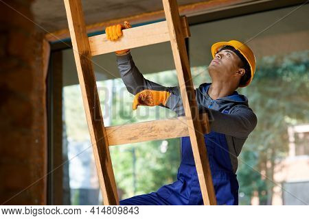 Young Male Builder In Overalls And Hard Hat Looking Focused, Climbing Up The Ladder While Working At