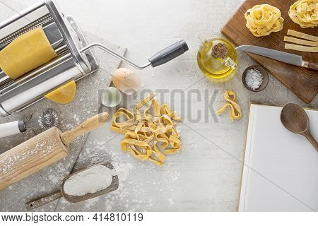 Making Homemade Fresh Pasta With Pasta Machine On Kitchen Table With Some Ingredients Around