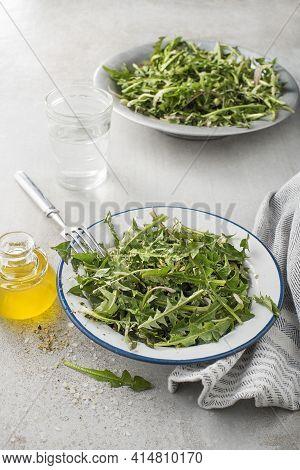 Fresh Dandelion Salad With Dressing. Healthy Spring Food Meal.