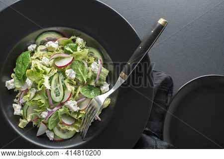 Healthy Green Salad With Fresh Vegetables And Fresh Cheese On Black Background Close Up