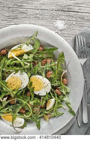 Fresh Dandelion Salad With Beans And Eggs On Wooden Background
