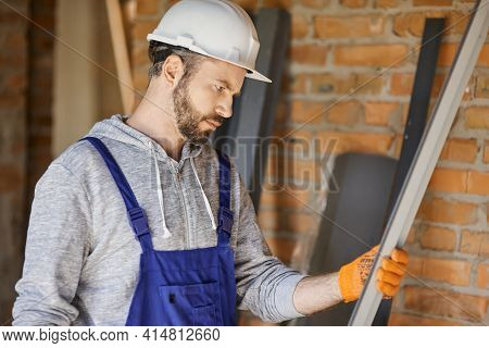 Portrait Of Focused Male Builder Wearing Overalls And Hard Hat Holding A Metal Stud For Drywall On I