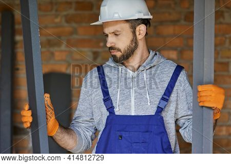 Young Male Builder Wearing Overalls And Hard Hat Looking Focused, Holding Metal Studs For Drywall Wh