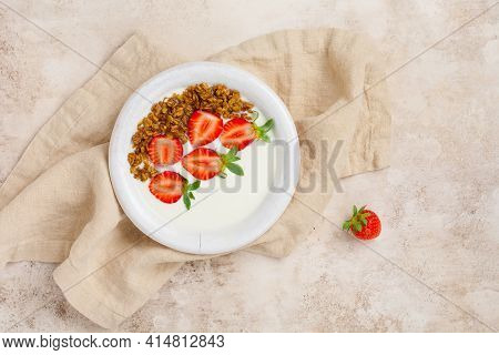 Greek Yogurt In White Bowl With Ingredients For Making Breakfast Granola And Fresh Strawberries On O