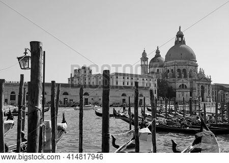 Gondolas and The Santa Maria della Salute church across the Grand Canal in Venice, Italy. Black and white venetian cityscape