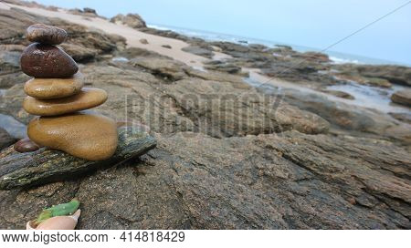A Rock Cairn On A Beach In Ghana, West Africa. Next To A Seashell With A Cactus In It.