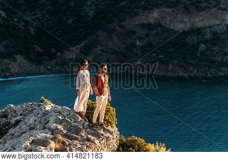 A Man Embraces A Beautiful Woman On The Edge Of A Cliff By The Sea. A Happy Couple Meets The Dawn By