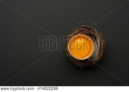 Egg Yolk Into Nest On Dark Background. Top View. Flat Lay. Easter Celebration