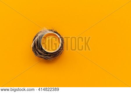 Egg Yolk Into Nest On Yellow Background. Top View. Flat Lay. Easter Celebration
