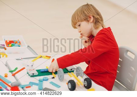 Little Boy Kid Child Constructor Checking Technical Toy. Children Robotics Constructor Assemble Robo