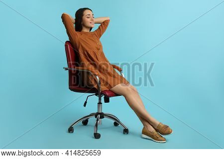 Young Woman Relaxing In Comfortable Office Chair On Turquoise Background