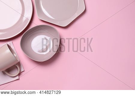 Set Of Ceramic Dishware On Light Pink Background, Flat Lay. Space For Text
