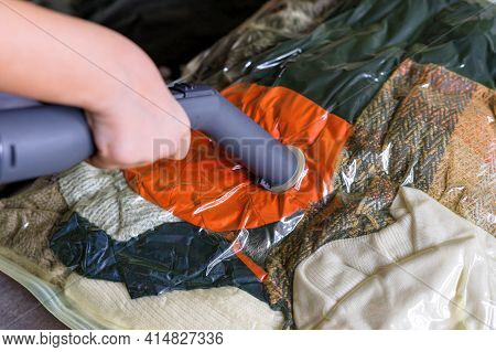 The Girl Pumps Out Air With A Vacuum Cleaner From A Vacuum Bag With Clothes. The Concept Of Storage