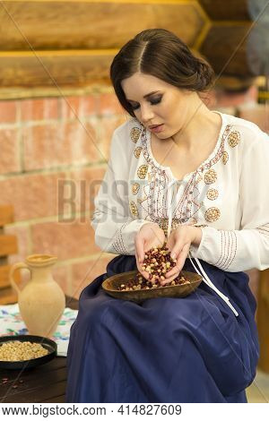 Sensual Caucasian Female In Rural Dress Holding  Bunch Of Frigole Beans In Hands
