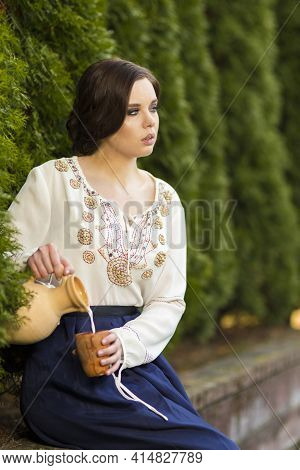 Relaxing Sexy Caucasian Girl In Rural Decorated Dress Pouring Milk In Front Of Line Of Fir-trees