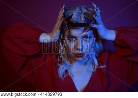 Portrait In Neon Of A Woman In A Silver Crown With Chains. The Girl In The Role Of The Princess. Fas