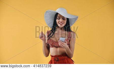 Happy Woman In Straw Hat And Swimsuit Chatting On Mobile Phone Isolated On Yellow.