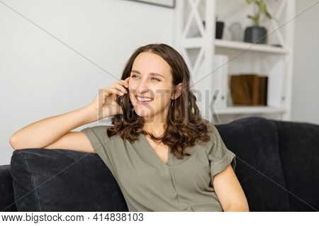 Hilarious Young Woman Talking By Smartphone Sitting On The Sofa At Home, Happy Charming Girl Enjoys