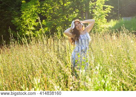 Happy Young Woman With Long Hair In Hat And Dress Walking Through The Summer Forest On A Sunny Day.