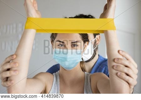 Young Woman Making Rehabilitation Shoulder Exercises Using Elastic Band, With Physiotherapist In A C