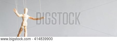 Human Control Concept. Wooden Puppet Doll On The Clothesline On A Gray Background With Copy Space.