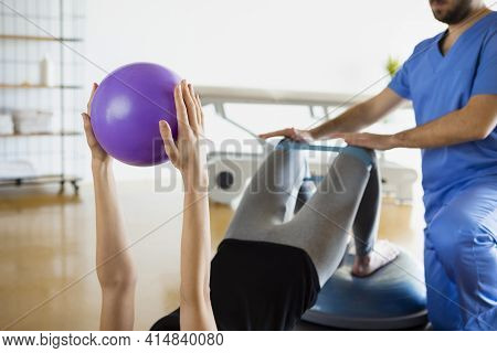 Detail Of Woman's Hands Holding Purple Fitness Ball During Recovery Session In A Medical Center Or L