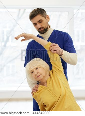 Senior Patient While Exercise Treatment With Her Experienced Physiotherapist. Rehab At A Medical Cen