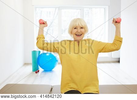 Positive Senior Woman Lifts A Dumbbell, Doing Treatment Exercise For Strengthening Arm Muscles And D