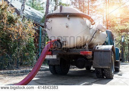 Close-up Pipe Hose Of Sewage Truck Car Engine Emptying Home Sewerage Tank. Septic Cleaning Vacuum Se
