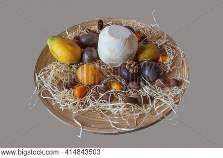 Exotic Fruits Are Laid Out On A Round Wooden Plate, With A Young Coconut To Drink In The Center. The