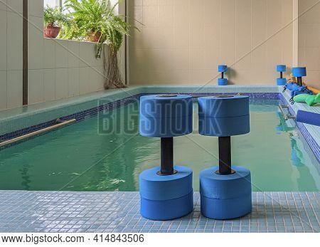 Two Dark Blue Dumbbells Stand Upright On The Banks Of A Small Aqua Aerobics Pool. Waterobics, Aquati