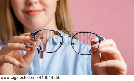 Eyeglasses in hands. Blue fashionable metal glasses for vision in hands of smiling young woman. Eye health Checking, vision correction via Eyeglasses over pink color background. Long web banner.