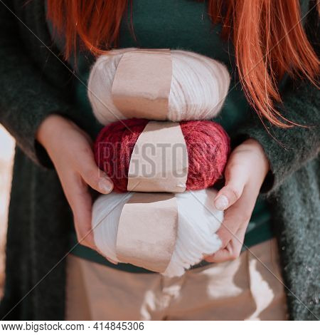 Female Hands Hold Colored Alpaca Yarn With Labels. Woolen Yarn For Knitting.
