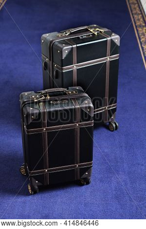 Two Suitcases With Luggage Are On The Carpet In Hotel. Comfortable Modern Luggage. Vertical Photo. B
