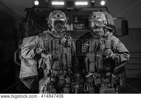 Two Men In Military Uniforms Stand In A Hangar With A Truck In The Background. Swat Concept.
