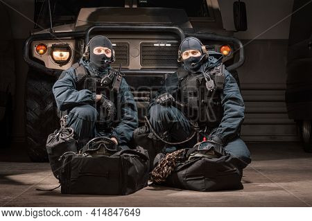 Two Uniformed Commandos Sit In A Hangar With A Military Truck In The Background. Swat Concept.