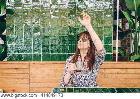 Stylish Young Beautiful Girl Raising Her Hand While Waiting For Coffee In A Coffee Shop
