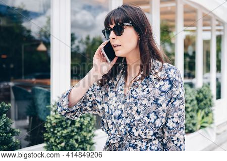 Beautiful Young Elegant Woman Walks Down The Street While Holding Her Cell Phone During A Call.