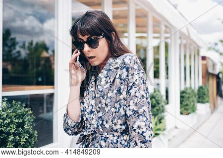 Young And Elegant Girl With A Surprised And Worried Expression During A Phone Call In The Street In