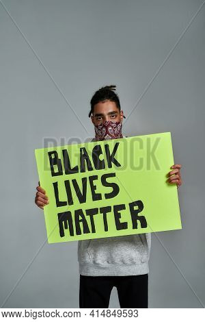 Young Gypsy Man Holding Placard With Anti Racism Quote And Looking At Camera While Posing On Light B