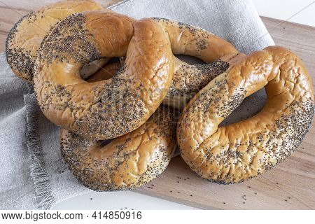 Several Delicious Bagels With Poppy Seeds On The Table In Close-up. Front View.