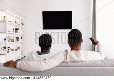 Black Couple Watching Tv And Using Remote Controller