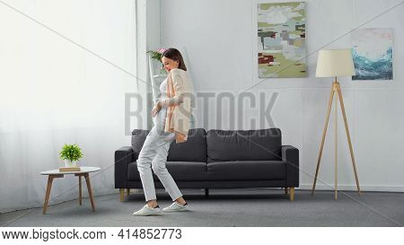 Cheerful, Pregnant Woman Touching Tummy While Dancing In Modern Living Room.